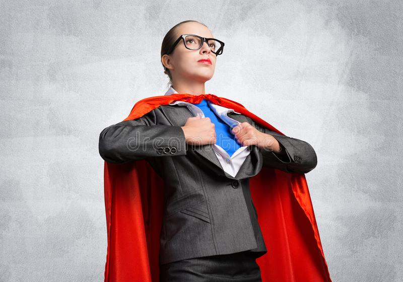 Attractive young business lady in red hero cape stock photos