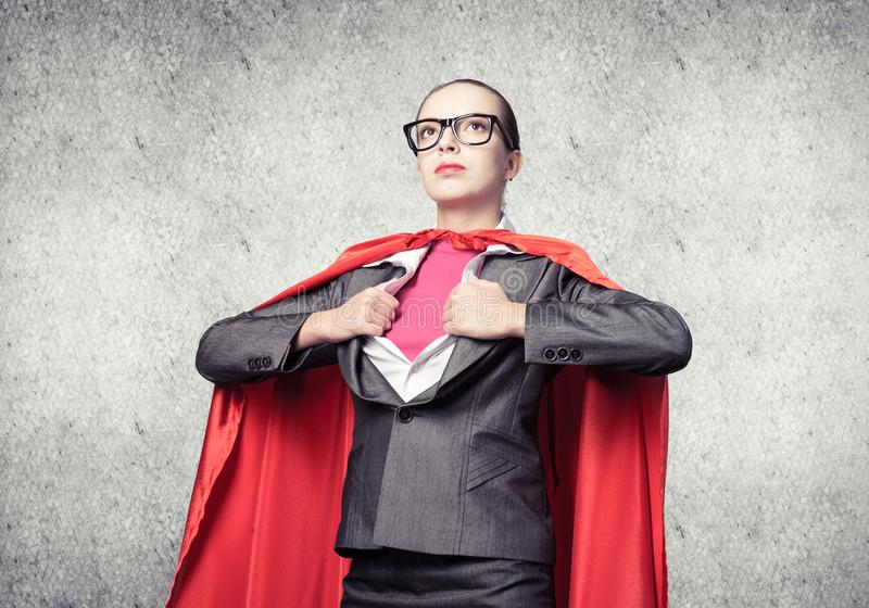 Attractive young business lady in red hero cape royalty free stock photos