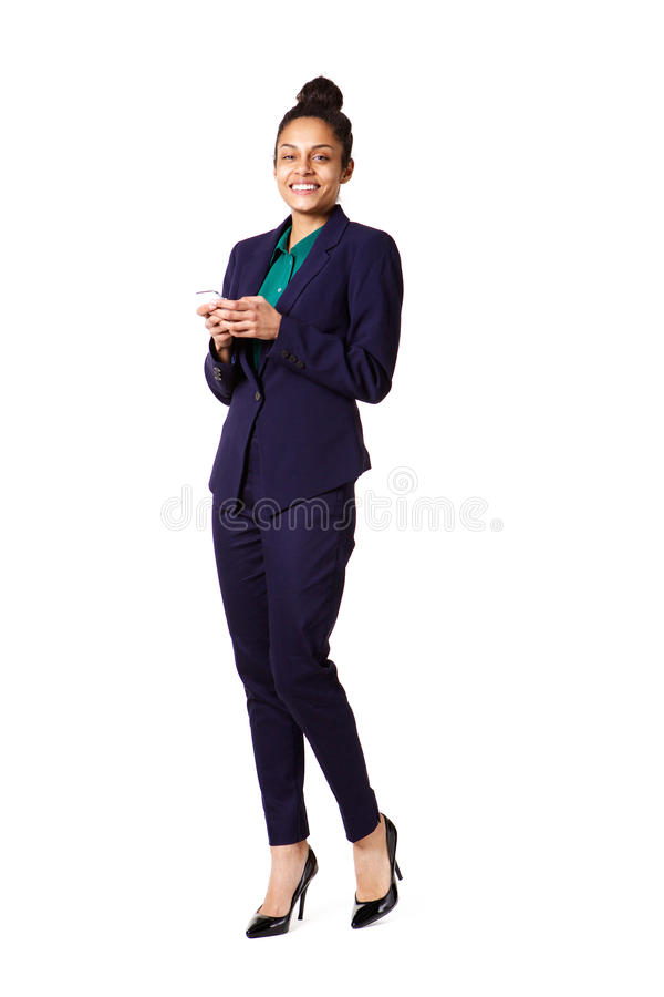 Attractive young business woman with a cell phone. Full length portrait of attractive young business woman with a cell phone standing over white background stock image
