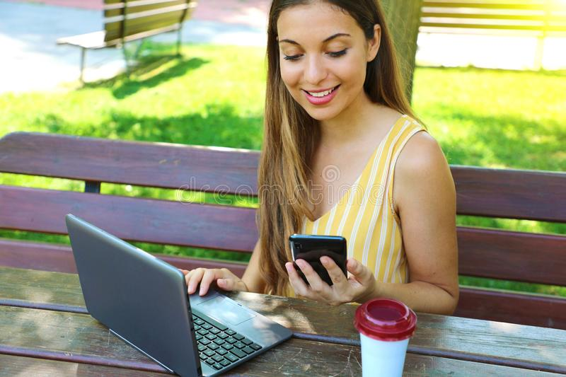 Attractive young business woman checking her phone while works at the laptop in the park stock photography