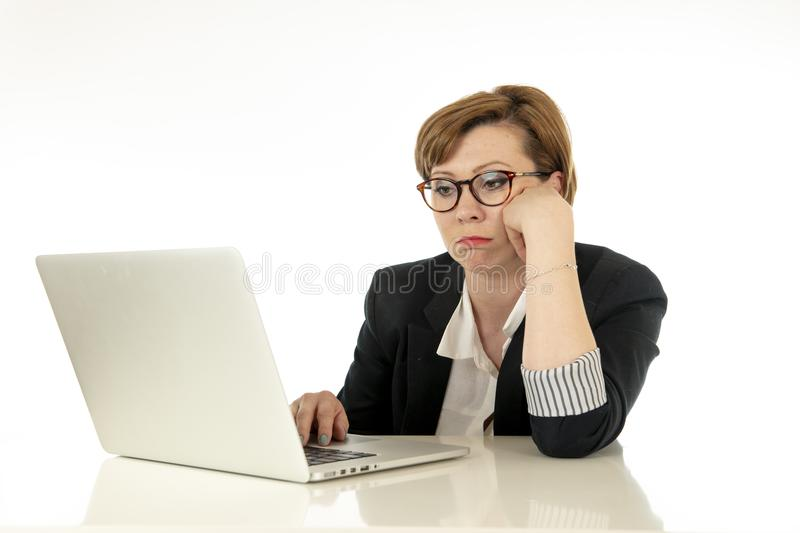 Attractive young business woman in glasses working on her computer stressed, tired and overwhelmed. stock photography