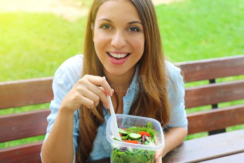 Attractive young business woman have a lunch sitting in city park looking at camera. royalty free stock images