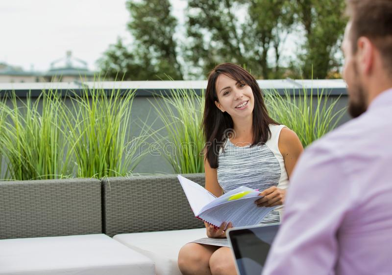 Attractive young business woman holding a file and smiling whilst she has a meeting outside wth a colleague who is working on his stock image
