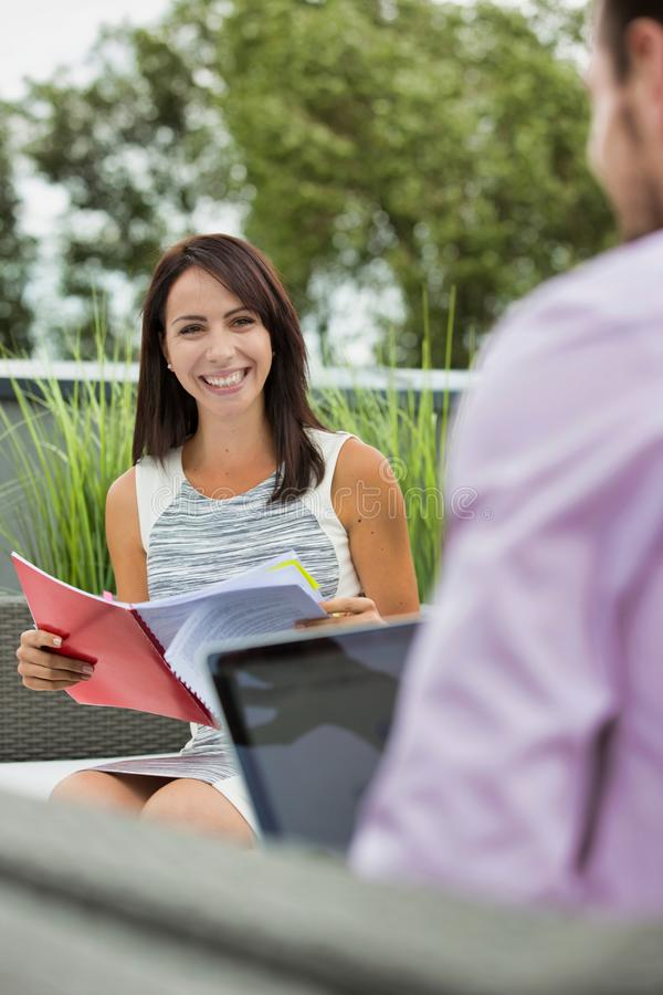 Attractive young business woman holding a file and smiling whilst she has a meeting outside wth a colleague who is working on his royalty free stock photography
