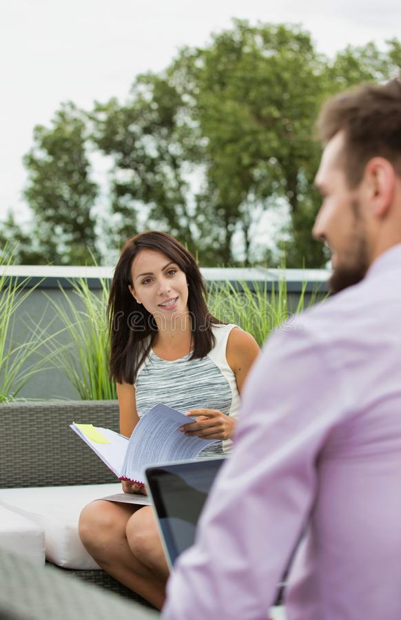 Attractive young business woman holding a file and smiling whilst she has a meeting outside wth a colleague who is working on his stock photos