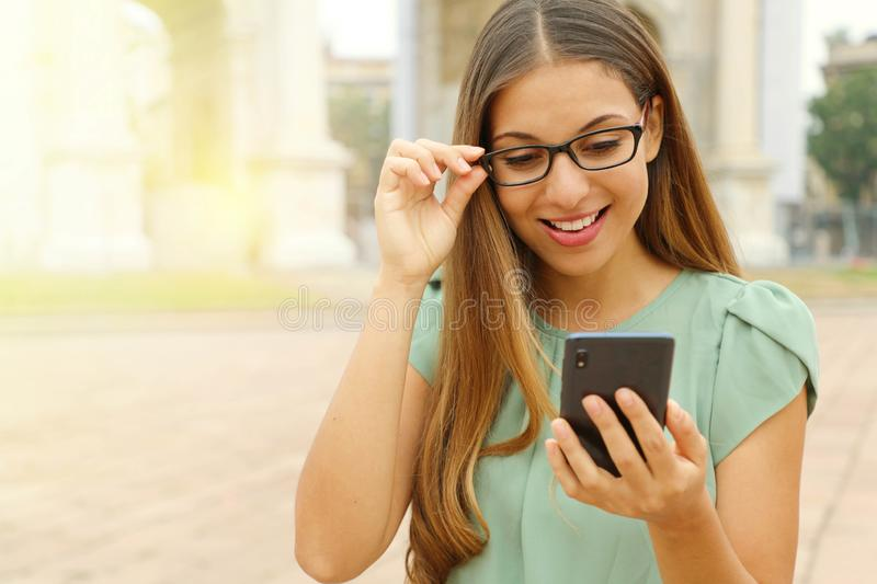 Attractive young business woman reading message on smart phone outdoor. Copy space stock photos