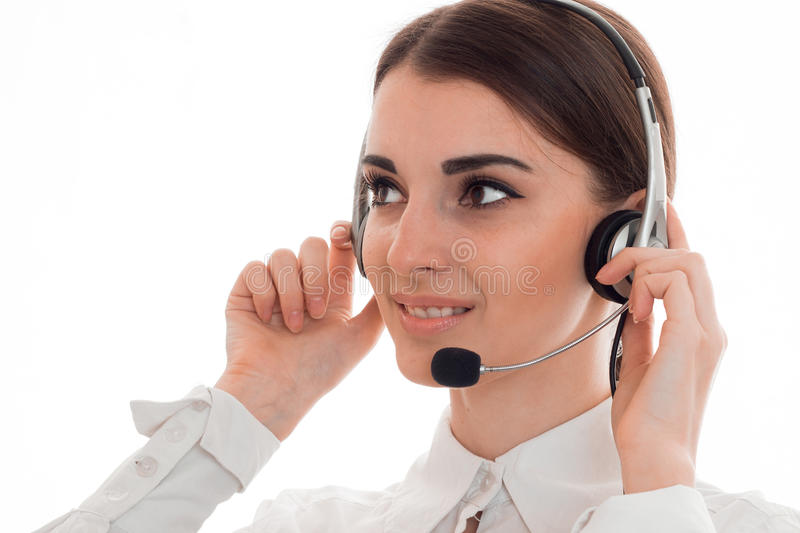 Attractive young business woman working in call center with headphones and microphone looking aside and smiling isolated royalty free stock image