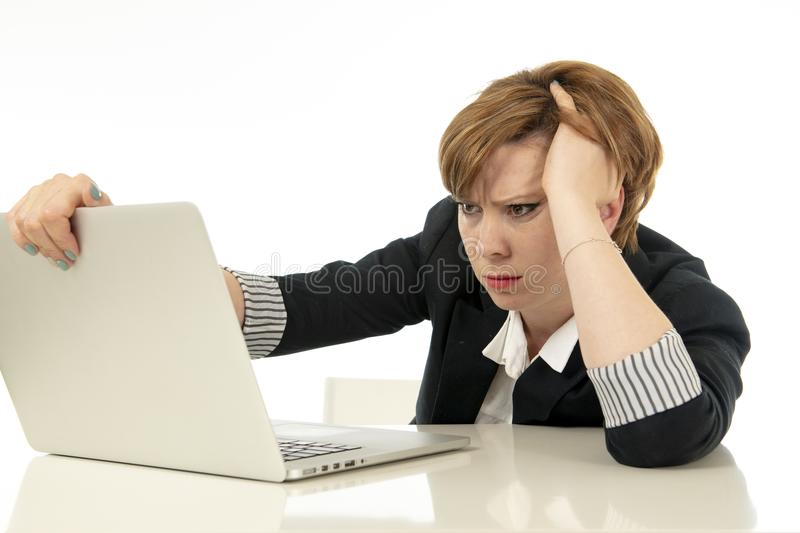 Attractive young business woman working on her computer stressed, unhappy and overwhelmed. stock photo