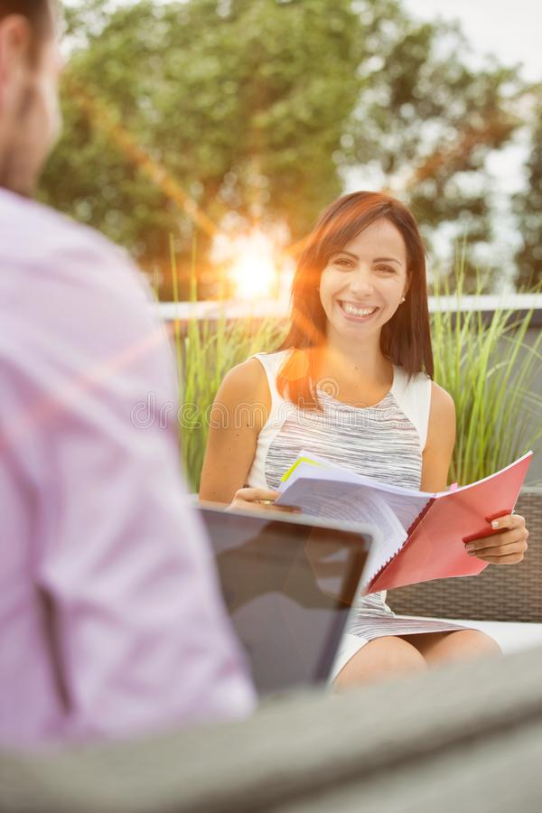 Attractive young business woman holding a file and smiling whilst she has a meeting outside wth a colleague who is working on his stock images