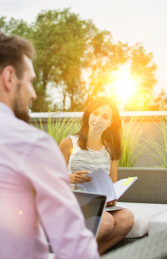 Attractive young business woman holding a file and smiling whilst she has a meeting outside wth a colleague who is working on his stock photo