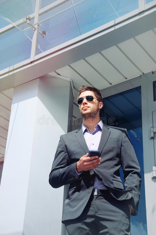 attractive young businessman with phone device on office building background, business concept stock image