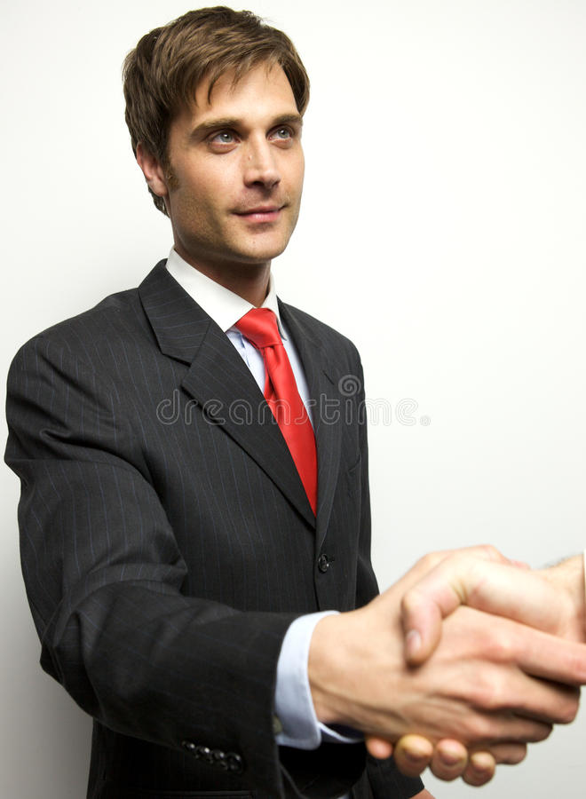 Attractive Young Businessman shaking hands. Off camera royalty free stock photography