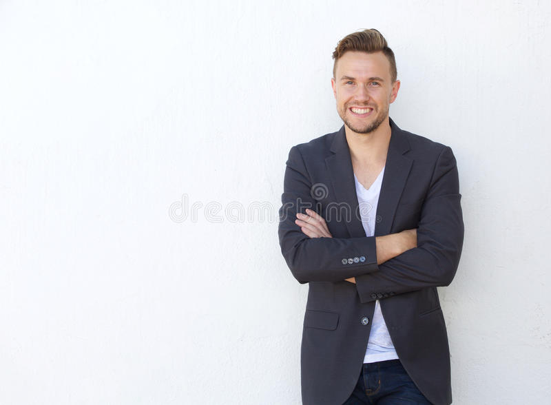 Attractive young businessman smiling against white wall. Portrait of attractive young businessman smiling against white wall royalty free stock images