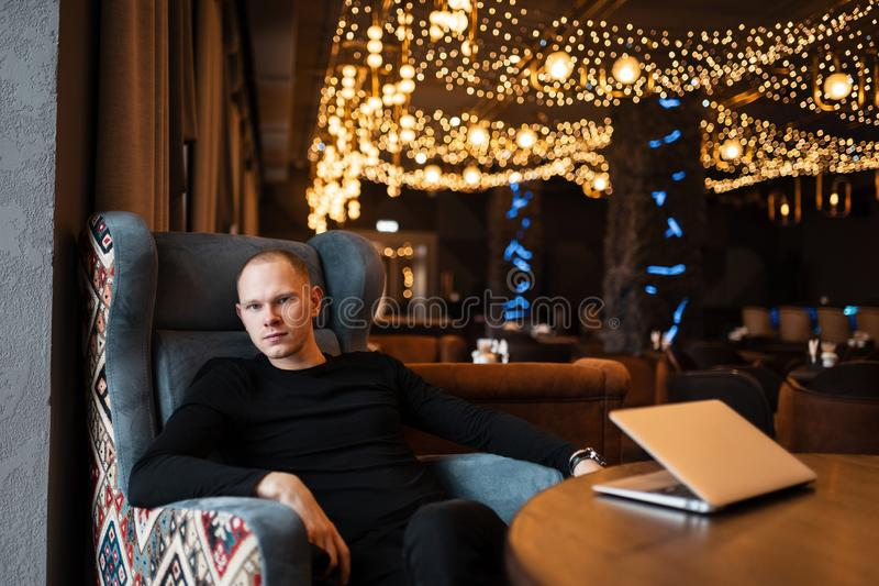 Attractive young businessman in stylish black clothes is working at a laptop while sitting in a luxurious restaurant. Work time. royalty free stock images