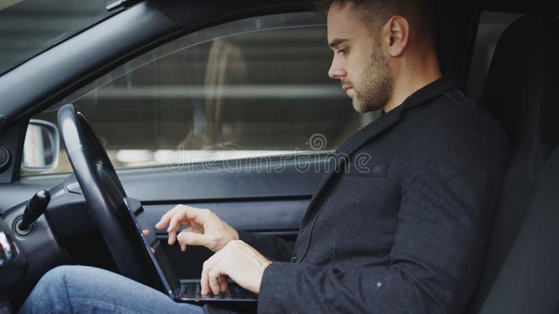 Attractive young man using tablet laptop computer while sitting inside his car outdoors stock images
