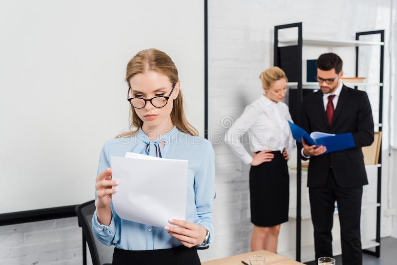 attractive young businesswoman with documents standing at modern office with colleagues stock photo