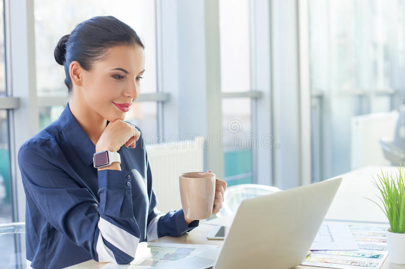 Attractive young businesswoman is enjoying hot tea royalty free stock photos