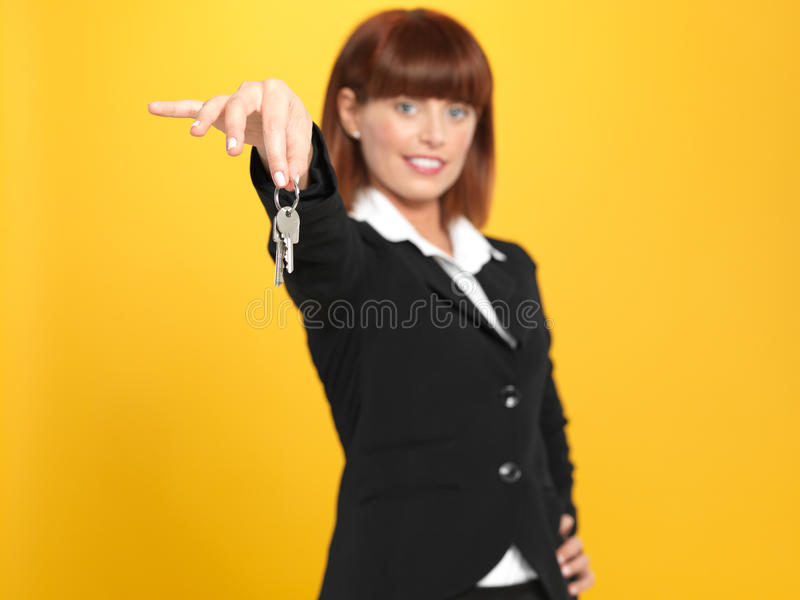 Attractive, young businesswoman holding house keys royalty free stock image