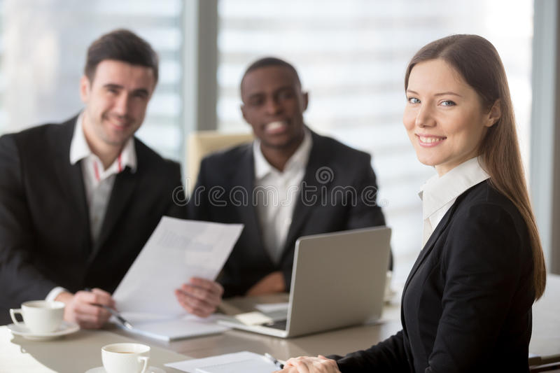 Attractive young businesswoman looking at camera, female team le royalty free stock photo