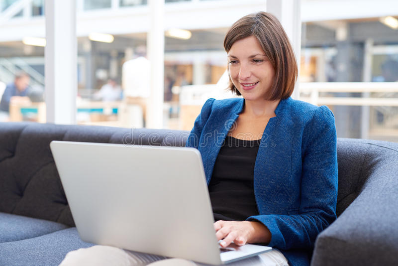 Attractive young busineswoman with laptop on couch in office. Busineswoman wearing a smart blue jacket smiling while working on her laptop computer in a modern royalty free stock images