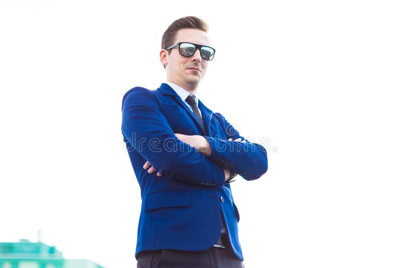 Attractive young busunessman in blue suit and sunglasses stand o stock image