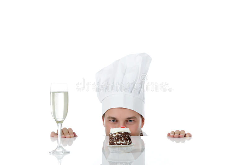 Attractive young caucasian man chef, temptation. Attractive young caucasian chef man being tempted, peeping above table. Studio shot. White background stock photography