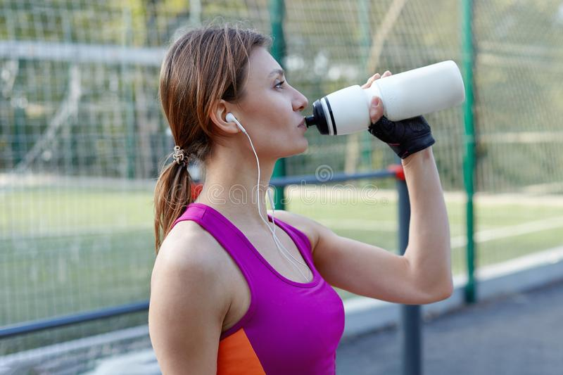 Attractive young caucasian woman in bright sportswear drinks water during fitness on outdoors sportsground. Active lifestyle woman royalty free stock photos