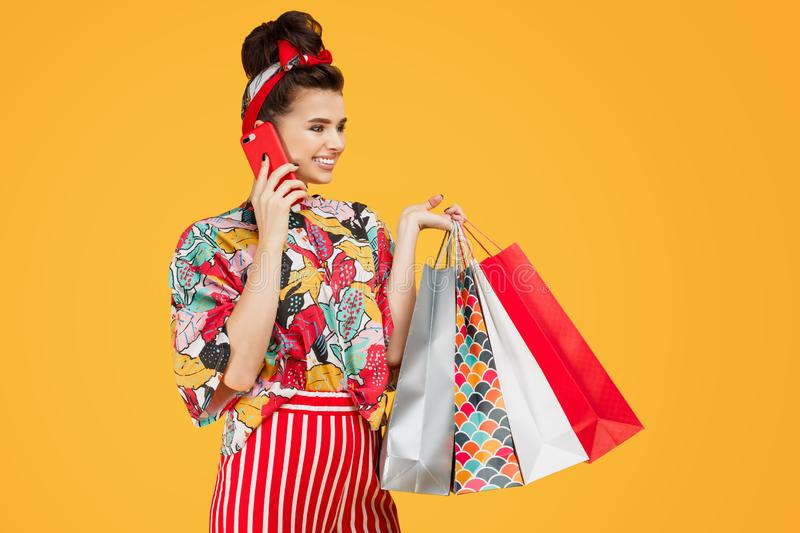 Attractive young caucasian woman in casual colorful clothes holding bags and shopping and talk on smartphone over orange stock image