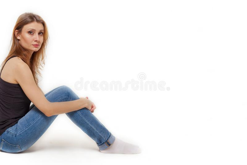 Attractive young caucasian woman with dark brown hair and eyes sits back to the wall, holding knees with a hands. Studio, white background, isolated, copy royalty free stock photography