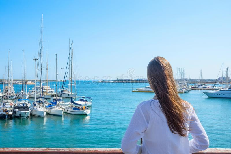 Attractive Young Caucasian Woman with Long Hair Boho Tunic Stands at Beach Looks at Yachts Sailing Boats Moored in Marina. Sea Sky royalty free stock image