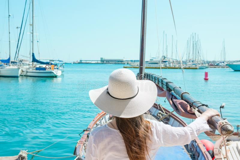 Attractive Young Caucasian Woman with Long Hair in Hat Stands in Vintage Sailing Boat Looks at Yachts Moored in Marina stock photos