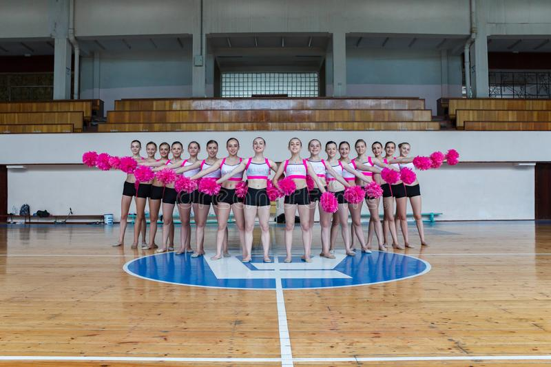 Attractive young cheerleaders working out in sports club, group of cheerleaders with pom-poms in their hands, hands to the side, royalty free stock photo