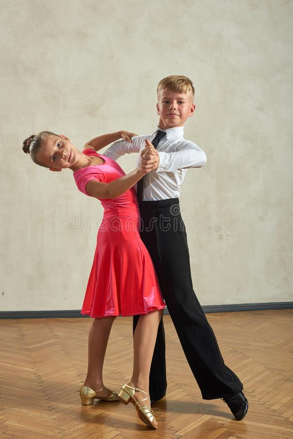 Attractive young couple of children dancing ballroom dance. In studio royalty free stock photo