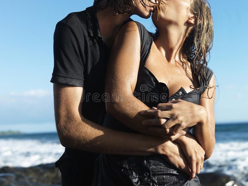 Attractive Young Couple Embracing and Kissing stock photo