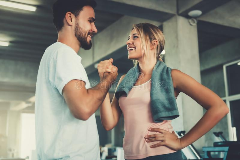 Attractive young couple handshaking after workout in fitness gym., Portrait of man and woman couple love are working out training royalty free stock photo