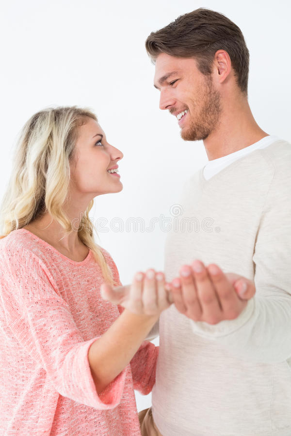 Attractive young couple holding out palms stock photo
