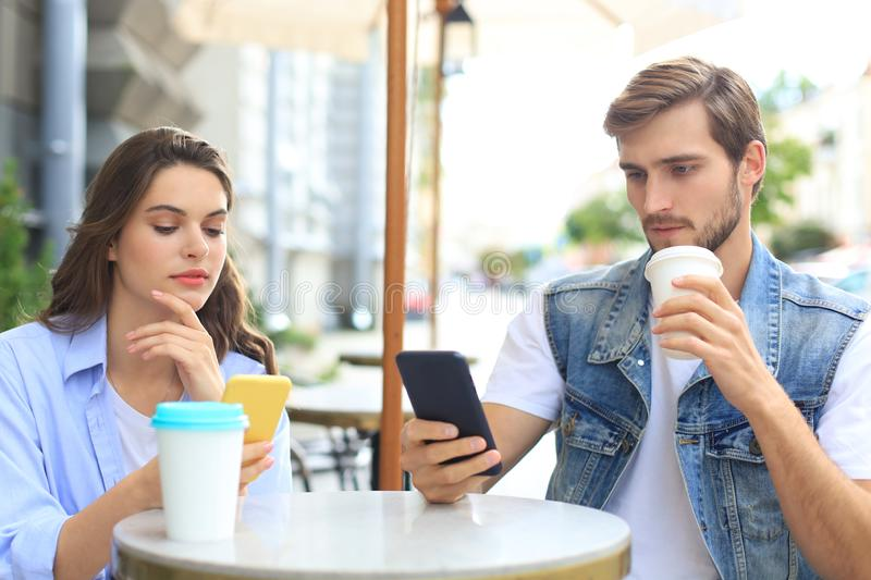 Attractive young couple in love drinking coffee while sitting at the cafe table outdoors, using mobile phone. royalty free stock images