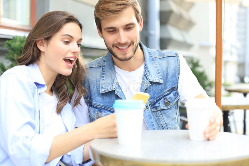 Attractive young couple in love drinking coffee while sitting at the cafe table outdoors, using mobile phone. stock images