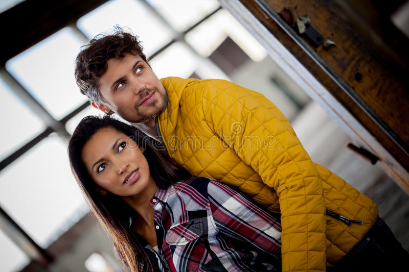 Attractive young couple in love. Attractive trendy young couple in love posing in a close embrace in an old commercial building looking to the side with a smile royalty free stock image