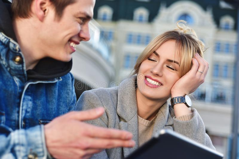 Happy couple or friends hugging and sharing a tablet in the street stock photos