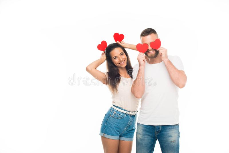 attractive young couple standing with red paper hearts, stock photography