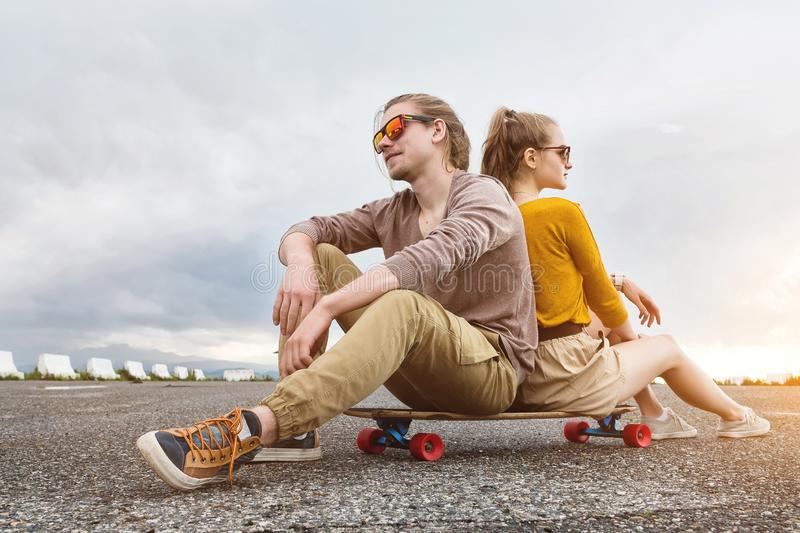 An attractive young couple in sunglasses sit back to back on their longboard in a suburban parking lot against a gray. Sky. The concept of a young family stock images
