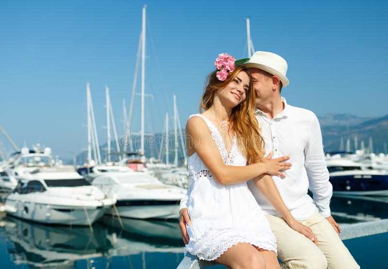 Attractive young couple walking alongside the marina with moored. Boats on a luxury waterfront in summer sunshine stock photos