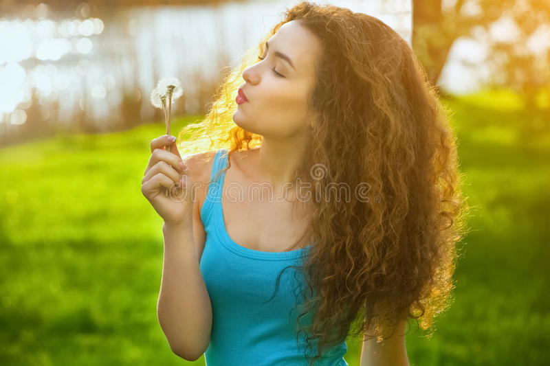 Attractive, young, curly girl in blue shirt, holding a dandelion blooming and smiling. royalty free stock photo