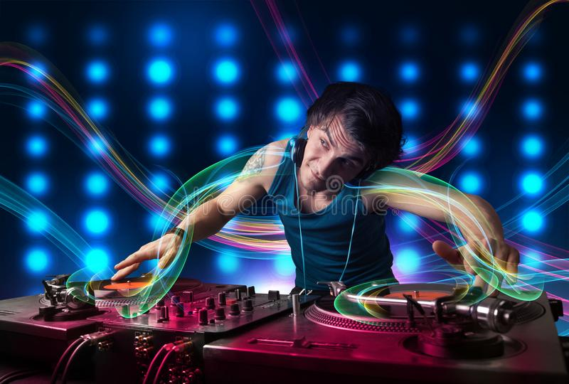 Young Dj mixing records with colorful lights royalty free stock photos