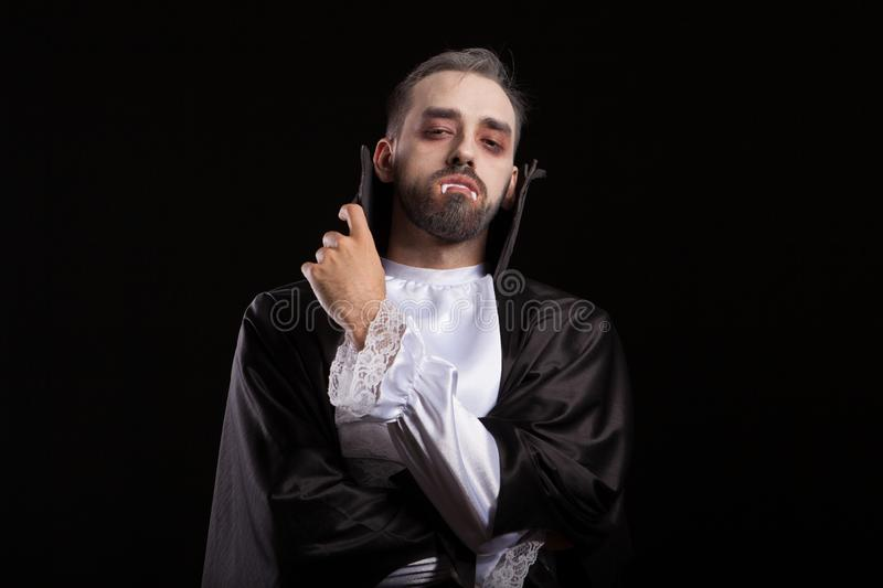 Attractive young Dracula keeping his arms crossed with his teeth out for halloween stock image