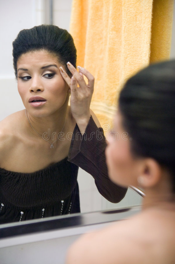 Attractive young ethnic girl applying make up royalty free stock images
