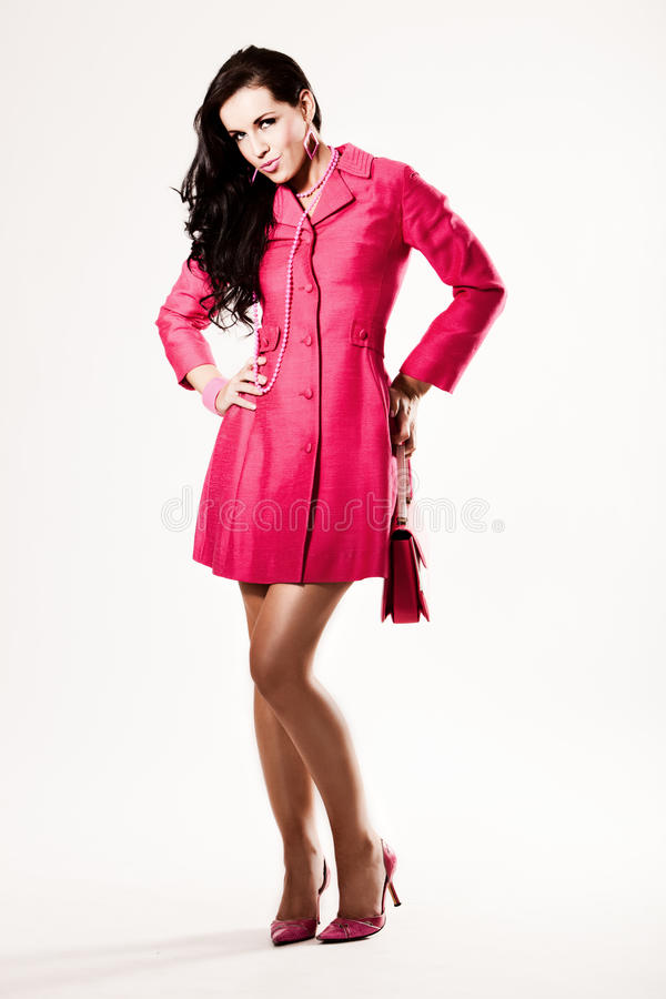 Attractive young fashion model in pink coat royalty free stock images