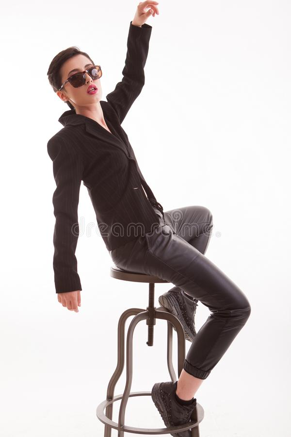 Attractive young fashion model posing with attitude sitting on a chair and looking at the camera in studio over white stock photo