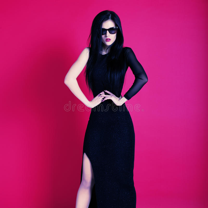 Attractive young fashion model posing in black dress and sunglasses royalty free stock photography